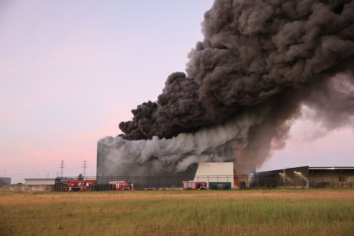 De dikke zwarte rookpluimen stijgen op uit het bedrijfspand.