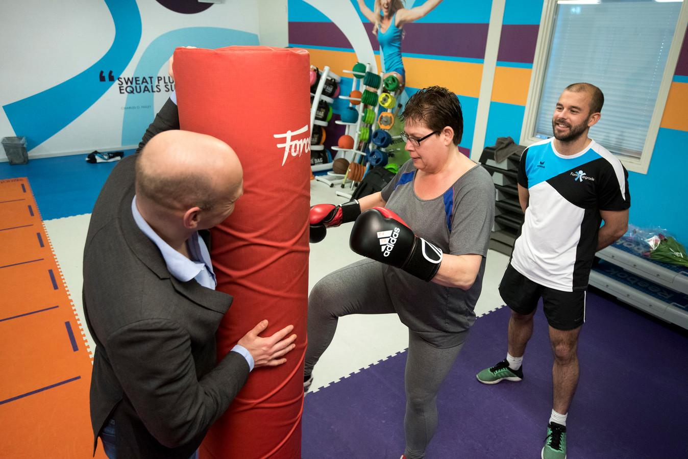 Lenie Polman geeft de bokszak een knietje bij X Fittt. Thomas Verheij moedigt aan, wethouder Gerrie Elfrink houdt de bokzak vast.
