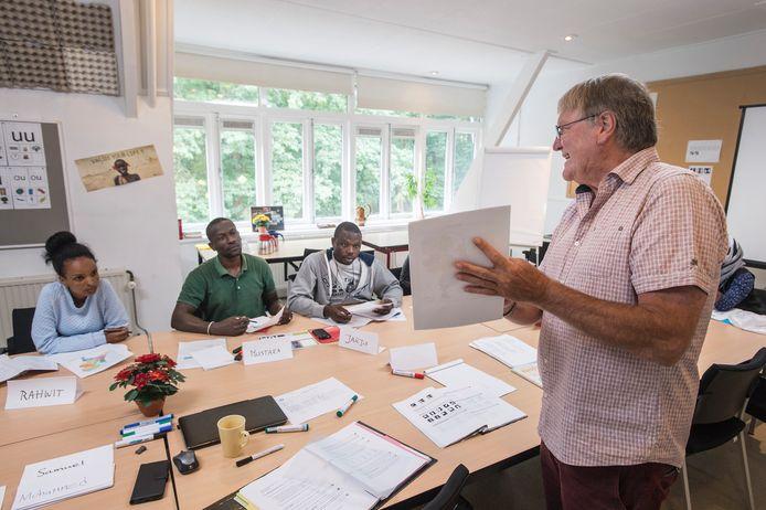 Oud-docent wiskunde en vrijwilliger Freek Gianotten in zijn klas op het azc waar hij taalles geeft. Mustafa, groene shirt, uit Sudan is een van de gedreven leerlingen voor basis Nederlands.