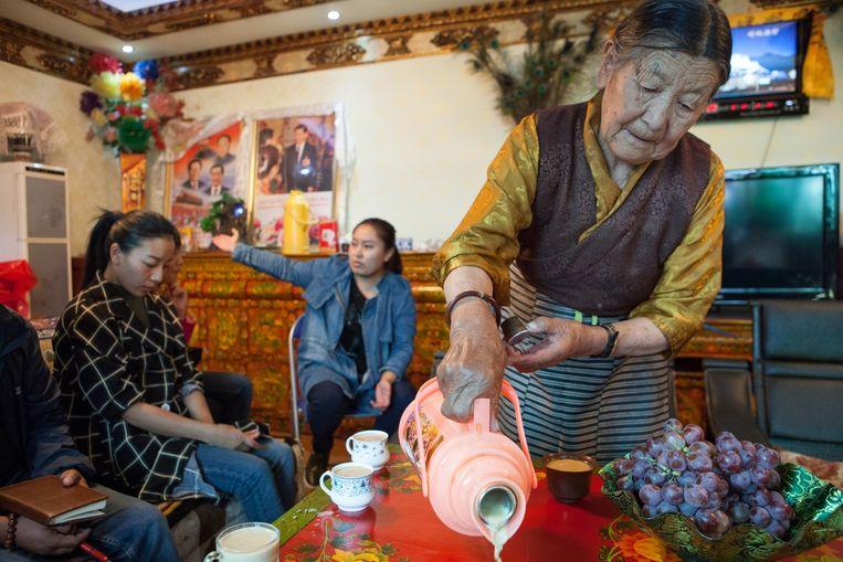 Oude vrouw die thee inschenkt is 'model familie' georganiseerd door de staat. Beeld Wassink Lundgren