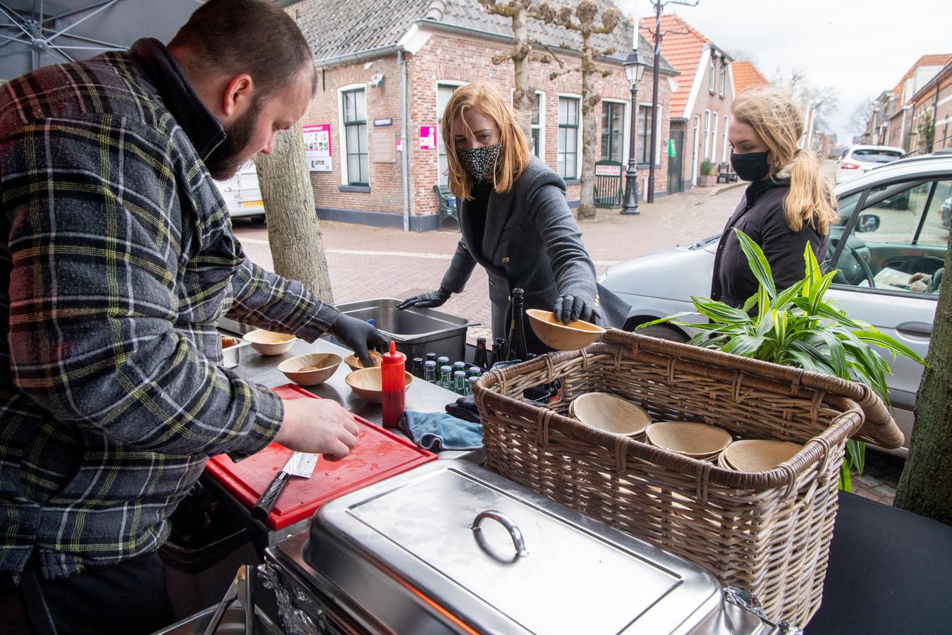Kok Christiaan Hakkers van restaurant De Woage in Gramsbergen bereidt een gerecht met langzaam gegaarde kip. Corine Klein en Indy Loopers (rechts) serveren het coronaproof aan de passerende deelnemers aan de Route Culinair du Vechtdal.