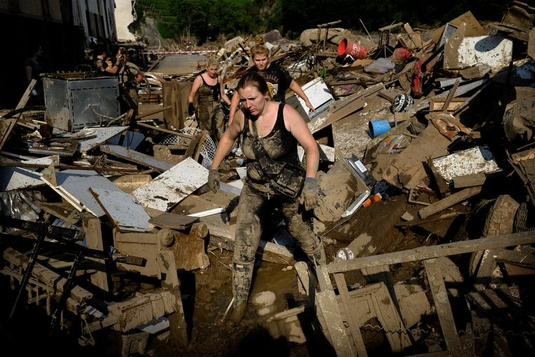 Inwoners en vrijwilligers banen zich een weg door de ravage die het acht meter hoge water heeft veroorzaakt. Beeld Daniel Rosenthal