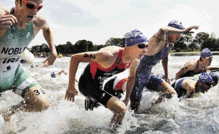 Sander Berk (midden) komt het water uit tijdens de EK triatlon in Holten. Berk was in het sterke veld de beste Nederlander met de 21ste plaats. De Spanjaard Javier Gomez pakte voor de tweede keer de Europese titel. (FOTO VINCENT JANNINK, ANP) Beeld ANP