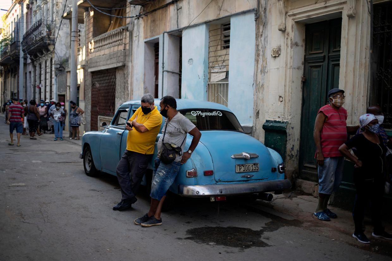 Een man kijkt op zijn gsm, voor de kruidenier staat een lange rij: na de protesten in Cuba is het voorlopig weer kalm in Havana. Beeld AP