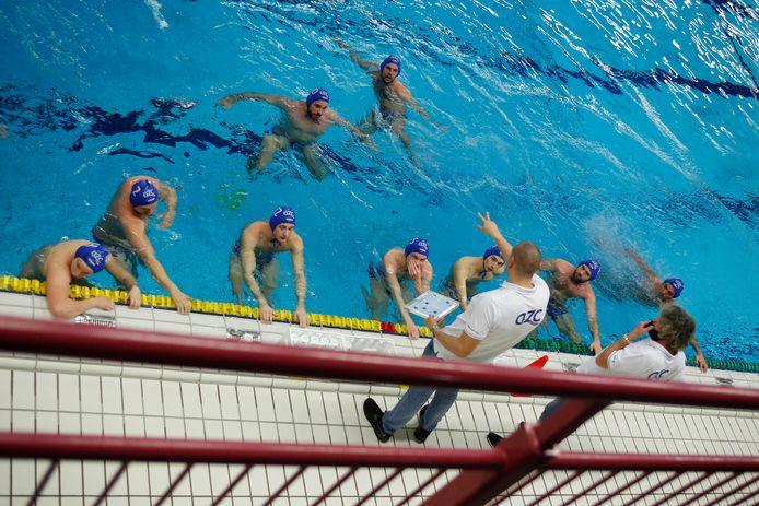 Coaches Yuri Szeles (links) en Ron van der Wild voorzien de waterpoloërs van AZC Alphen van aanwijzingen.