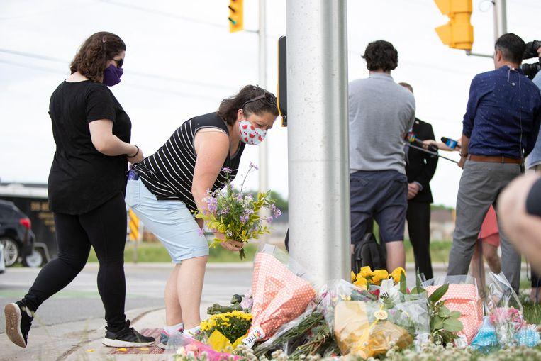 Mensen leggen bloemen neer op de plek waar het gezin opzettelijk werd doodgereden. Beeld AFP