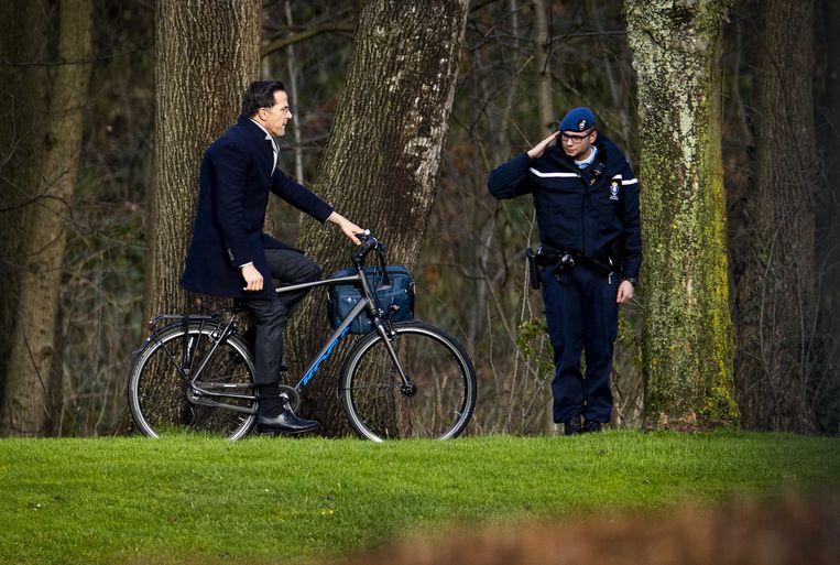 Een marechaussee salueert terwijl premier Mark Rutte op de fiets aankomt bij het Catshuis, voor het eerste kabinetsberaad over de affaire rond de kinderopvangtoeslag op de ambtswoning van de premier. Beeld ANP