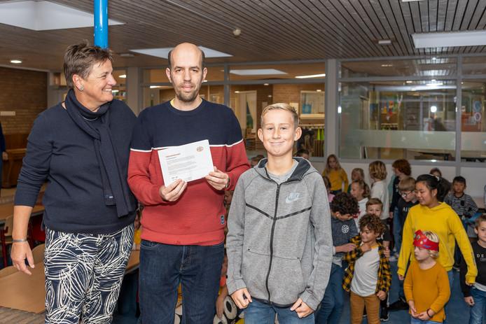 Conciërge Sander Vreeke (m) kreeg kaartjes voor de wedstrijd PSV-AZ voor zijn 20-jarig jubileum bij basisschool Stapelhof in Renesse. Naast hem schooldirecteur Ingrid Bijlsma en Fedde Raats die het cadeau overhandigde namens alle leerlingen en leerkrachten.
