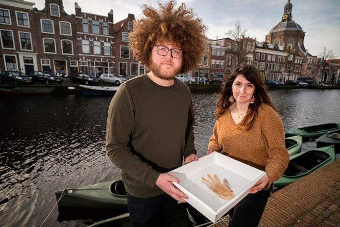 Wetenschappers Auke Florian-Hiemstra en Liselotte Rambonnet met een baarsje, gevangen in een handschoen