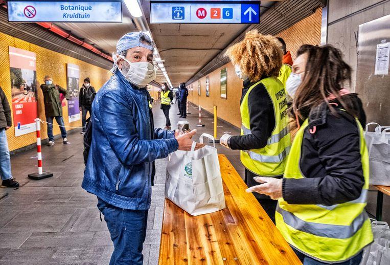 In metrostation Botanique delen vrijwilligers van Operatie Thermos maaltijden uit. Beeld Tim Dirven