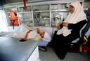 Een Palestijnse vrouw die gewond is geraakt bij een Israëlische luchtaanval wacht in een ambulance tot ze de grens met Egypte over mag