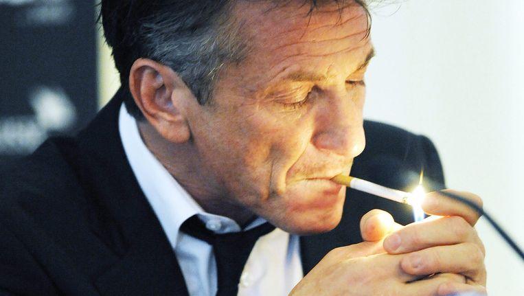 Acteur Sean Penn steekt een sigaret op tijdens een persconferentie in Zwitserland. (archieffoto) Beeld epa