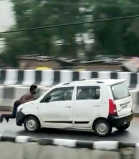 Une voiture roule avec un homme accroché au capot sur plusieurs kilomètres