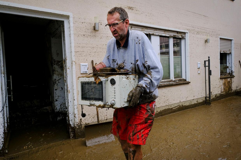 Een man draagt een microgolf naar buiten. Het duurt wellicht maanden tot jaren vooraleer het leven hier weer normaal wordt. Beeld (c) DANIEL ROSENTHAL