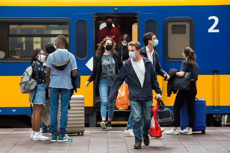 Reizigers op Rotterdam Centraal met verplichte mondkapjes.  Beeld Arie Kievit