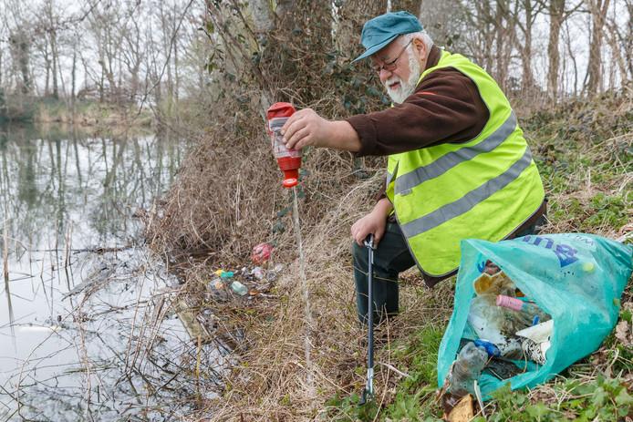 Bij en in de kolk langs de Hilligjesbergerweg wordt veel zwerfafval afval gevonden. Vrijwilliger Harry van Wijk vist in een paar minuten verschillende stukken afval uit het water. Foto: Pedo Sluiter