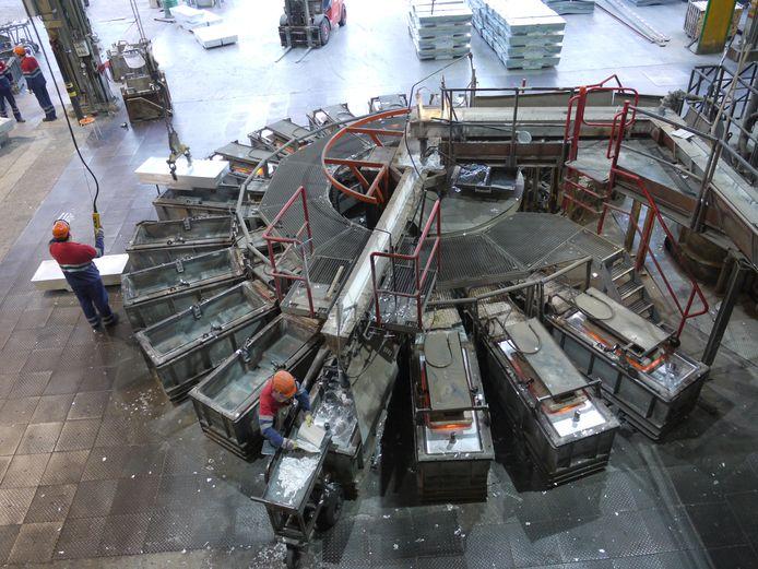 Gesmolten tin wordt in een carrousel van gietvormen tot zinkbroden van 2.000 kilogram gegoten.
