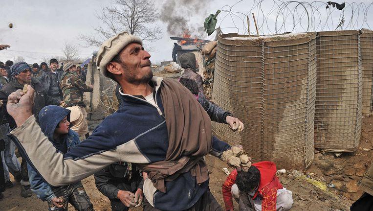 Afghaanse demonstranten gooien stenen bij de Amerikaanse basis in Bagram. Beeld AFP