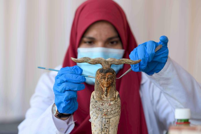 Een archeoloog maakt een standbeeld schoon tijdens de onthulling van de sarcofagen in Sakkara.