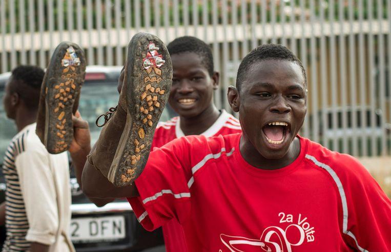 Migranten laten hun schoenen met antislipzolen zien. Het is ze gelukt om in Mellila over het hek te klimmen naar Spanje. Beeld REUTERS