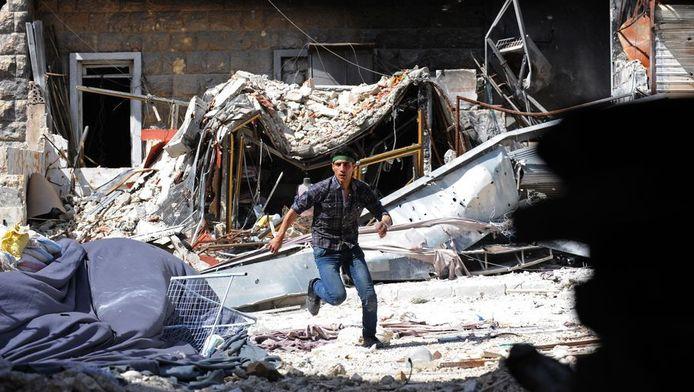 Een Syrische oppositiestrijder rent door Aleppo.
