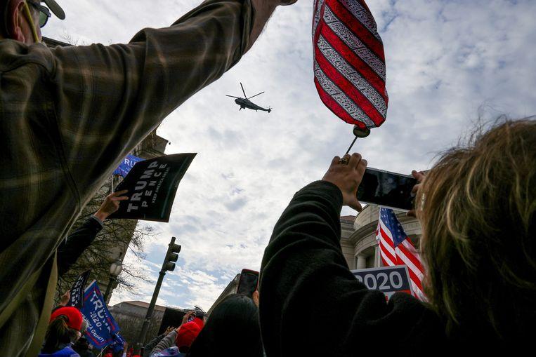 Gejuich als de helikopter Marine One, met president Donald Trump aan boord, over de menigte vliegt. Beeld REUTERS