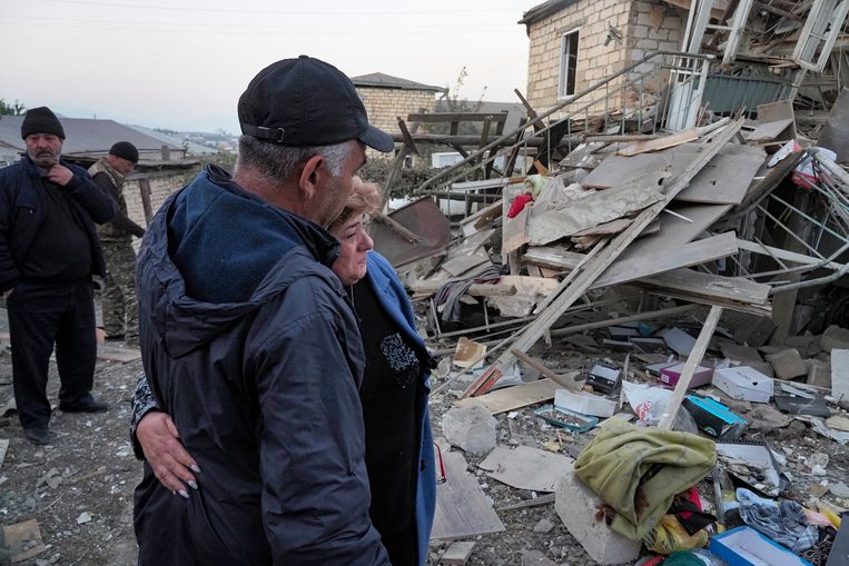 Inwoners verzamelen bij een verwoest gebouw na een militair conflict in Stepanakert, de separistische regio van Nagorno-Karabach.  Beeld AP