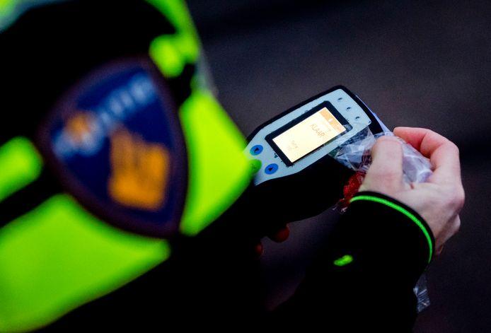 Een politieagent voert een alcoholcontrole uit.