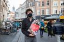 Martijn Droog, eigenaar van notenzaak Noten & Zo, met de poster in de Lange Hofstraat voor zijn notenzaak.