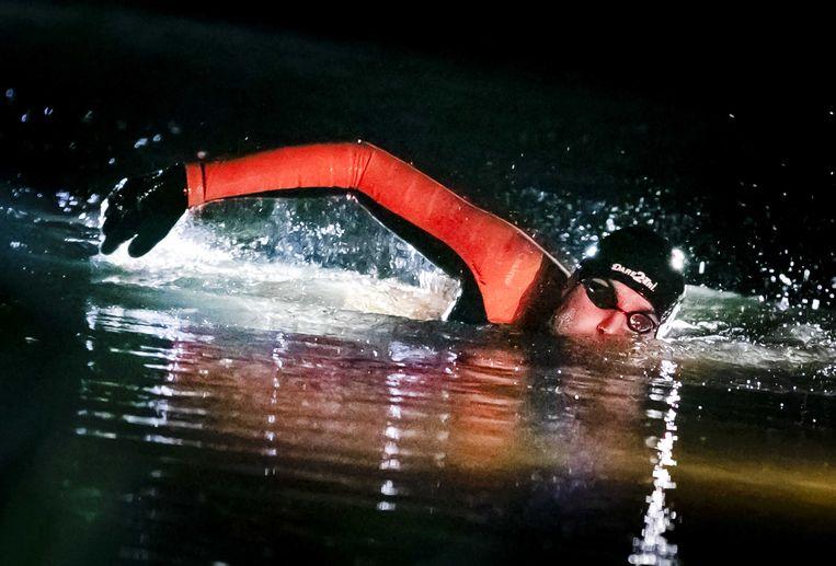 Zwemmer Maarten van der Weijden in het holst van de nacht onderweg tijdens zijn monstertocht langs de elf Friese steden.  Beeld ANP