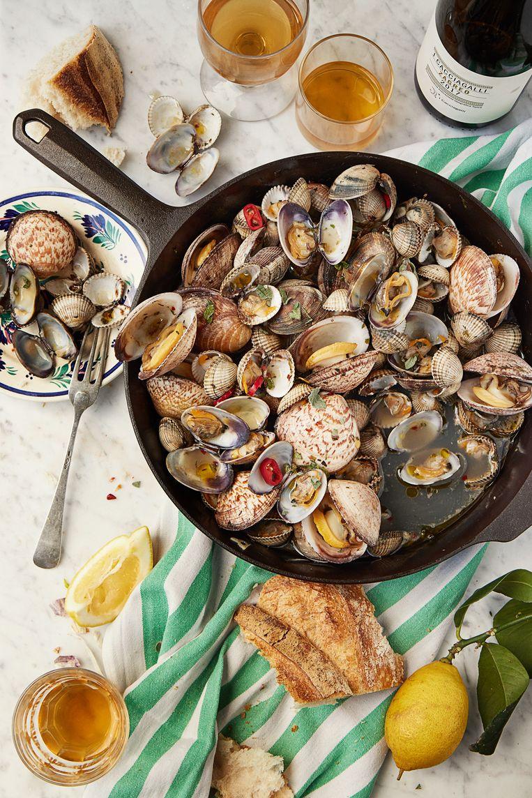 Schelpen uit de pan met Napolitaanse kruiden. Beeld