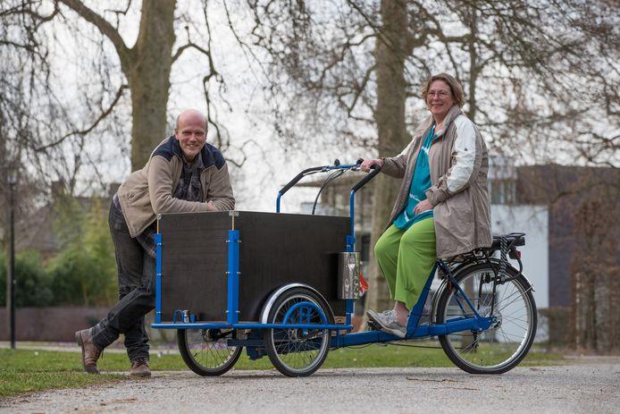 Martha Beeker en Paul Hendriksen van Stichting Goede Buren, met een van de (bak)fietsen waarmee de spullen worden bezorgd. Beeker: ,,We hopen alles in het gunstigste geval op 19 juni bij de mensen te kunnen afleveren.''