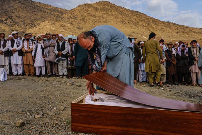 Een man neemt afscheid van Zemari Ahmadi tijdens zijn massabegrafenis waarbij hij en meerdere van zijn familieleden werden begraven.