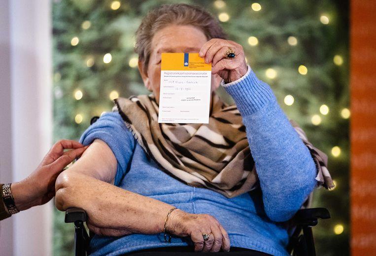 Een verpleeghuisbewoner in Zoetermeer laat haar vaccinatiekaart zien. Beeld ANP