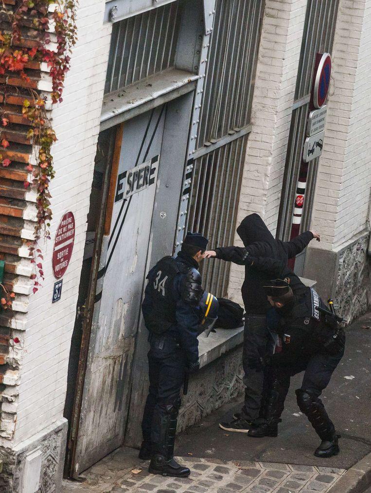 Een man wordt gefouilleerd na een inval in Le Pre-Saint-Gervais. Beeld AFP