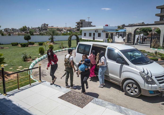 Leden van Koerdische veiligheidstroepen begeleiden drie kinderen die in de Syrische stad Qamishli zijn overgedragen aan Nederlandse diplomaten.