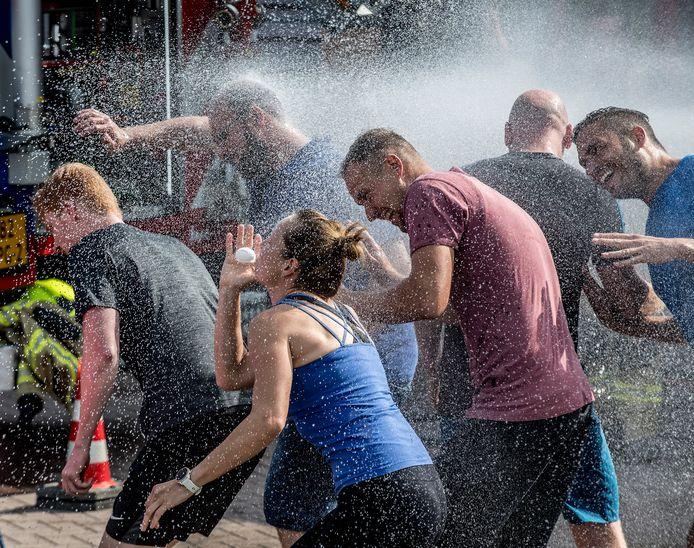 De Valburgse brandweer probeert een ei uit mond van vrouwelijke deelnemer te spuiten, maar zij wordt beschermd door teamgenoten.