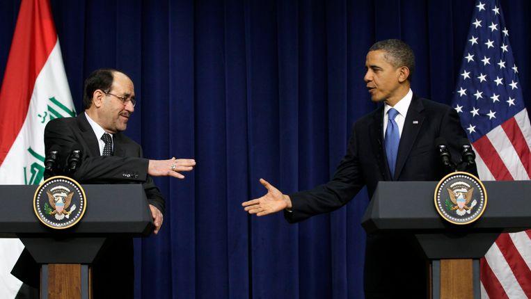 De Iraakse premier Nouri al-Maliki (links) en Amerikaanse president Barack Obama staan op het punt elkaar de hand te schudden in het Witte Huis in 2011. Beeld AP