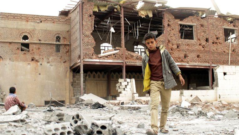 Een jongetje loopt tussen de ruïnes van voormalige woonhuizen in de stad Aden. Beeld afp