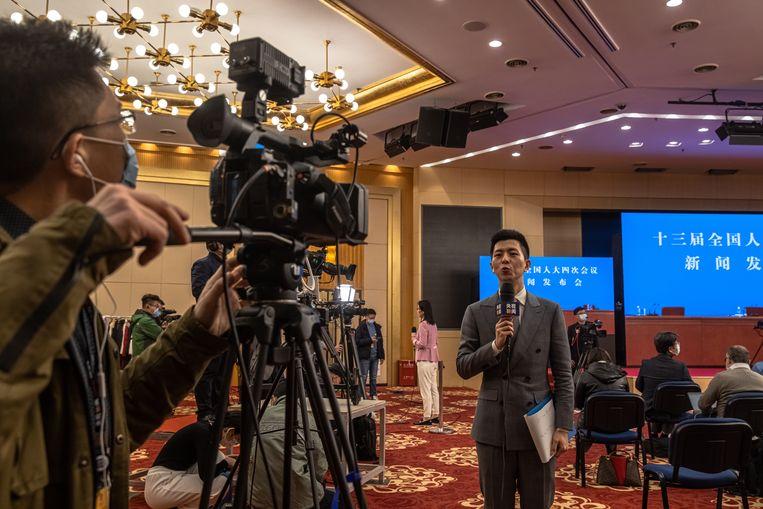 Een Chinese verslaggever bericht over de persconferentie bij de start van de Volksvergadering in Beijing. Beeld EPA