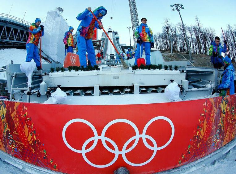 Vrijwilligers maken de skischans bij het Russki Gorki Jumping Center schoon. Beeld epa
