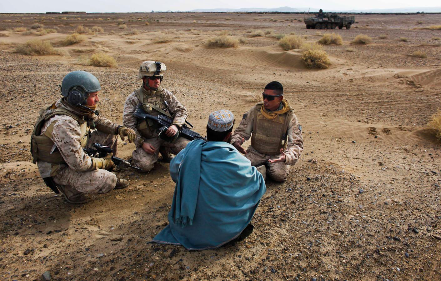 Twee Amerikaanse militairen spreken met een Afghaanse man in 2009 met behulp van een lokale vertaler (uiterst rechts).