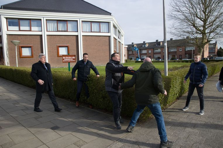 De man in spijkerbroek en groene jas is een beveiliger van de NOS (ook aanwezig om verslag te doen) die ingrijpt nadat een journalist van RTV Rijnmond is aangevallen bij een gereformeerde kerk in Krimpen aan den IJssel.  Beeld Arie Kievit