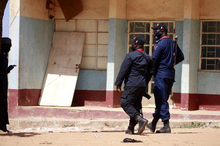 Politieagenten aanwezig bij de school in Kankara waar de jongen zijn ontvoerd.  Beeld Reuters