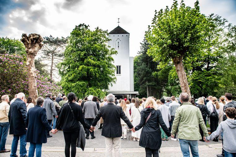Mensen houden elkaars hand vast tijdens een rouwplechtigheid voor Julie Van Espen. Beeld BELGA