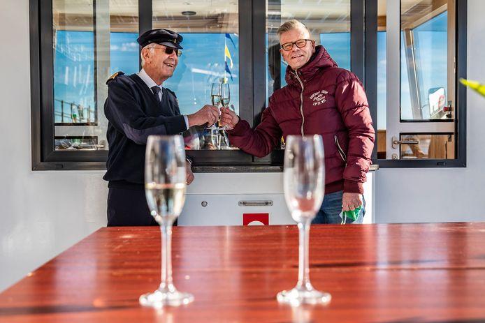 Geert Scheers (links) toast met wethouder Frits Rorink op de nieuwe pont. Een elektrische heen-en-weer.