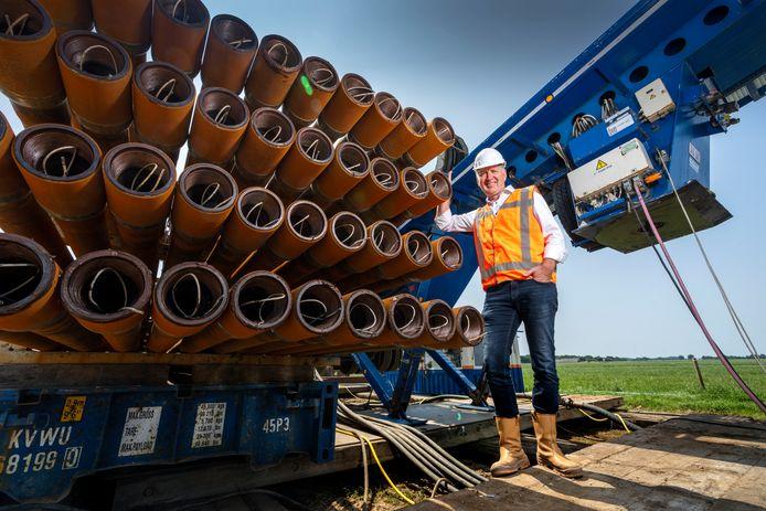 Projectleider Robert-Jan Niewenhuis bij de boorinstallatie. Met deze buizen wordt plaats gemaakt voor de nieuwe leiding die boven de grond klaar ligt.