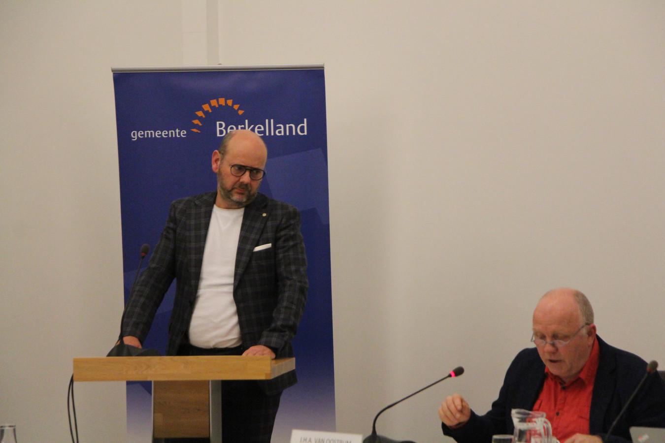 GroenLinks-fractieleider Leo Morren achter de microfoon om de motie van treurnis toe te lichten. Hans Pelle valt in als voorzitter van de gemeenteraad.