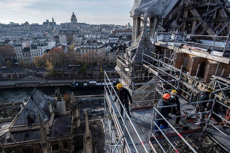 Arbeiders aan het werk bij de reparatie van de kathedraal Notre-Dame in Parijs, die vorig jaar zwaar werd beschadigd door een brand. Beeld AFP