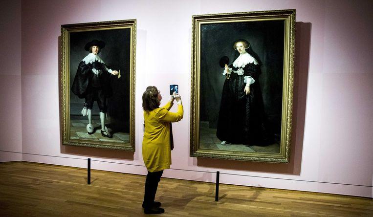Een bewonderaar staat voor 'Portret van Marten Soolmans' (links) en 'Portret van Oopjen Coppit' (rechts) van Rembrandt, bij een eerdere expositie in het Rijksmuseum.  Beeld EPA